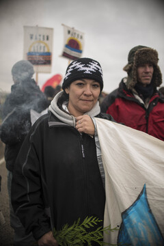 Dani from Montana holds cedar, a sign of peace while being blessed and cleansed by a cloud of Sage at a peaceful protest near one of the barricades.
